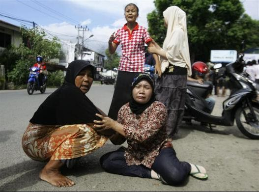 "Fig. 1.0 ""Stunned residents in Aceh Province lay on the streets fearing for more violent shakings and panick-stricken others evacuate to higher grounds in anticipation of a Tsunami.  Image Courtesy: Reuters."""